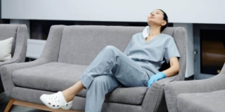 Photo of a tired healthcare professional resting on a grey couch