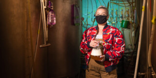Ellie Hadley, wearing a bright red patterned jacket, stands in a brewery in front of pipes and fermenters. She smiles under her mask.