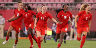 Soccer players on Canada's national team celebrate after winning gold at the Olympics.