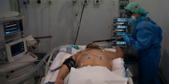 A nurse checks on man on his belly in a hospital bed. He is hooked up to a ventilator.